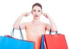 Покупатель женщины покрывая ее уши с указательными пальцами Стоковое Изображение RF