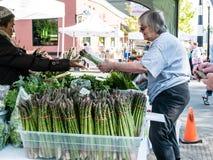 Покупатель покупает пачку спаржи на рынке фермеров, Corvallis, Oreg Стоковые Изображения RF