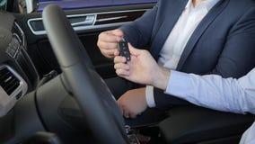 Покупатель получает ключ от продавца автомобиля, рукопожатия, всхода конца-вверх рук, автоматического дела, мужчины с автодилером сток-видео