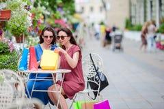 2 покупателя моды красочных с сумками ходя по магазинам с умным телефоном в улице Продажа, защита интересов потребителя и концепц Стоковая Фотография RF
