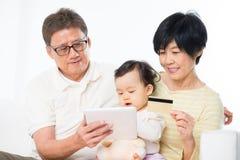 Покупка азиатской семьи он-лайн Стоковое Изображение