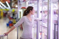 Покупка молодой женщины для мяса в гастрономе Стоковое Фото