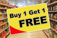 Покупка одно получает один свободный желтый ярлык на абстрактной предпосылке супермаркета Стоковая Фотография RF