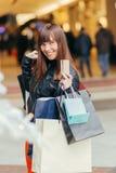 покупка рождества Красивая счастливая девушка с кредитной карточкой в магазине Стоковые Изображения