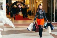 покупка рождества кладет красивейшую счастливую женщину в мешки покупкы C Стоковое Фото