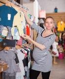 Покупки беременной женщины в магазине одежды для младенцев Стоковые Фотографии RF