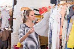 Покупки беременной женщины в магазине одежды для младенцев Стоковые Изображения