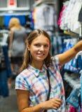 Покупки девочка-подростка для одежд внутри магазина одежды Стоковое Изображение