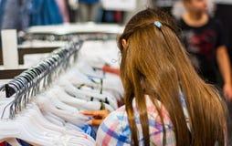 Покупки девочка-подростка для одежд внутри магазина одежды Стоковые Изображения RF
