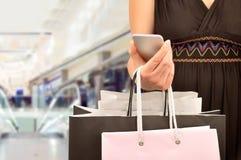 Покупки женщины используя мобильный телефон Стоковые Изображения