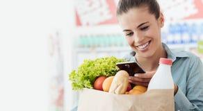 Покупки женщины и отправка СМС с ее телефоном Стоковое фото RF