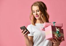 Покупки женщины онлайн с мобильным мобильным телефоном для подарков подарков на рождество усмехаясь на свете - пинке стоковое фото