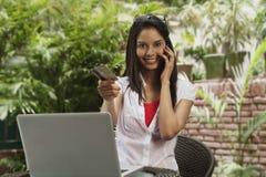 Покупки женщины онлайн и говоря на мобильном телефоне Стоковые Изображения