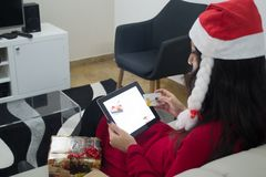 Покупки женщины рождества Санты онлайн на софе Стоковое фото RF