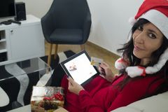Покупки женщины рождества Санты онлайн на софе Стоковое Изображение