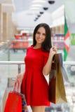Покупки молодой женщины в моле с хозяйственными сумками Стоковые Изображения