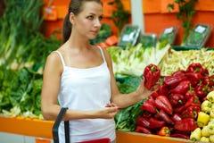 Покупки молодой женщины в супермаркете в отделе плодоовощ Стоковые Фото