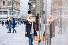 Покупки окна женщины в центре города Зима стоковая фотография