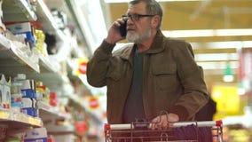 Покупки пенсионера в супермаркете, говоря по телефону Человек делает приобретение в отделе сыров сток-видео