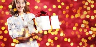 Покупки рождества, женщина с пакетом подарка на запачканном ярком li Стоковое фото RF