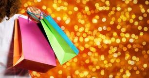 Покупки рождества, женщина с сумками на запачканном ярком bac светов Стоковые Изображения