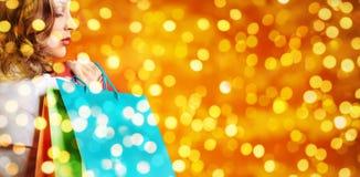 Покупки рождества, женщина с сумками на запачканном ярком bac светов Стоковое Изображение RF