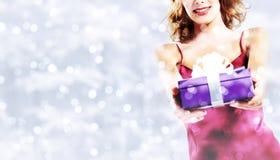 Покупки рождества, усмехаясь женщина с пакетом подарка на запачканном b Стоковое Фото