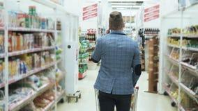 Покупки человека на супермаркете и говорить по телефону, взгляду задней стороны, steadicam сняли акции видеоматериалы