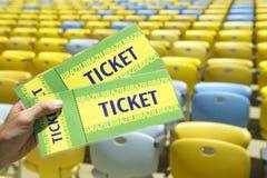 Поклонник футбола держа 2 билета Бразилии на стадионе стоковая фотография rf