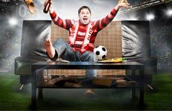 Поклонник футбола на софе стоковая фотография