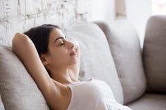 Полагаться молодой женщины ослабляя назад на удобной софе стоковые фотографии rf