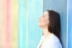 Полагаться расслабленной женщины отдыхая на красочной стене стоковая фотография rf