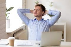 Полагаться удовлетворенного бизнесмена ослабляя назад, наслаждающся перерывом на w стоковое фото rf
