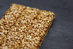 Полезные закуски Еда диеты фитнеса Boletchik от семян подсолнуха kozinaki, баров энергии Черная текстурная верхняя часть предпосы стоковое фото rf