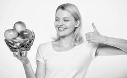 Полезный и вкусный i сад, девушка садовника с корзиной яблока Счастливая женщина есть яблоко farming стоковые изображения
