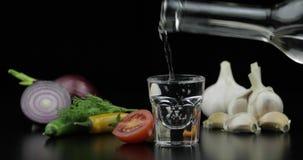 Полейте водку напитка алкоголя от бутылки в стопке Предпосылка с овощами видеоматериал
