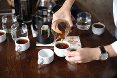 Полейте свеже заваренный кофе от стеклянного кувшина на белых чашках Стоковое Фото