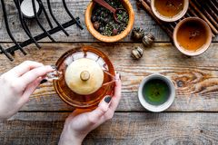 Полейте чай от бака чая Чашки, сухие листья чая на деревенском деревянном взгляд сверху предпосылки Стоковые Изображения RF