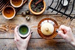 Полейте чай от бака чая Чашки, сухие листья чая на деревенском деревянном взгляд сверху предпосылки Стоковое Изображение