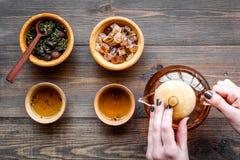 Полейте чай от бака чая Чашки, сухие листья чая на темном деревянном copyspace взгляд сверху предпосылки Стоковая Фотография RF