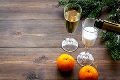 Полейте шампанское в кануне Нового Года 2018 Стекла, tangerine, елевая ветвь на деревянном copyspace предпосылки Стоковые Изображения