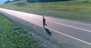 Полет малой высоты перед sporty человеком на совершенной дороге асфальта акции видеоматериалы