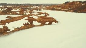 Полет над карьером с замороженными озерами воды Холмы песка и ледистой поверхности воды акции видеоматериалы