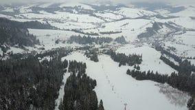 Полет над лыжным курортом в прикарпатских горах Вид с воздуха покрытых снег домов в горах видеоматериал