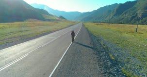 Полет над туристом автостопщика идя на дорогу асфальта Огромная сельская долина на летнем дне Парень рюкзака пеший сток-видео