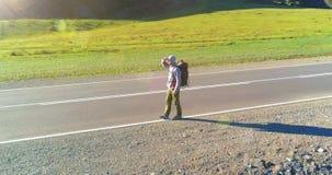 Полет над туристом автостопщика идя на дорогу асфальта Огромная сельская долина на летнем дне Парень рюкзака пеший акции видеоматериалы