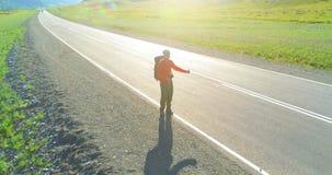Полет над туристом автостопщика идя на дорогу асфальта Огромная сельская долина на летнем дне Парень рюкзака пеший видеоматериал
