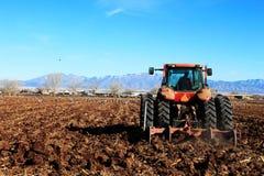 поле вспахивая трактор Стоковое Фото