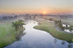 Поле для гольфа зеленого цвета вида с воздуха с заходом солнца и туманом в утре стоковые изображения