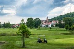 Поле для гольфа на старой предпосылке церков стоковые фото